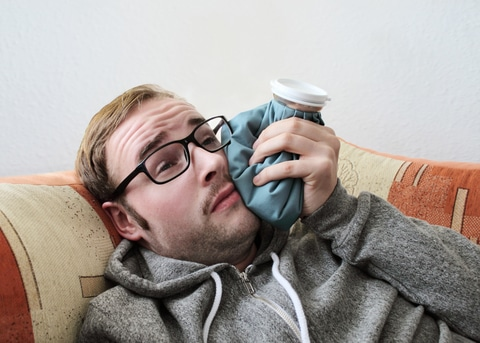 Man with a toothache holds a cold compress against his face
