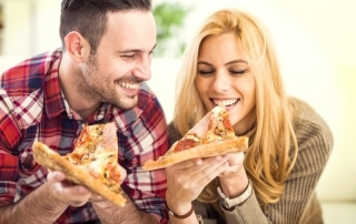 Happy couple eating pizza together