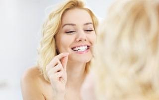 Woman flossing her teeth in a mirror
