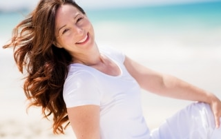 Brown haired woman enjoys the breeze at the beach