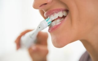 Female brushing her teeth with an electric toothbrush