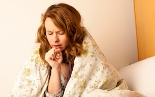 Red haired woman with a cold sits up in bed coughing
