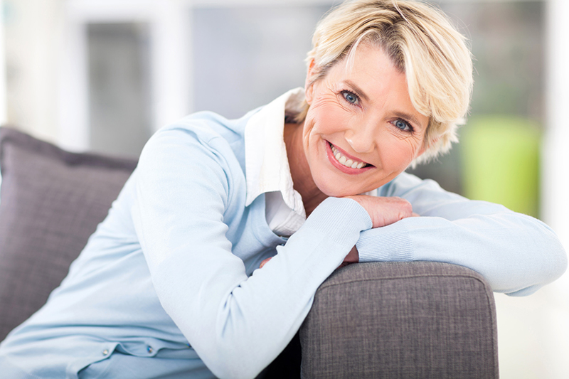 Middle aged blonde woman leans on the arm of a couch in her living room
