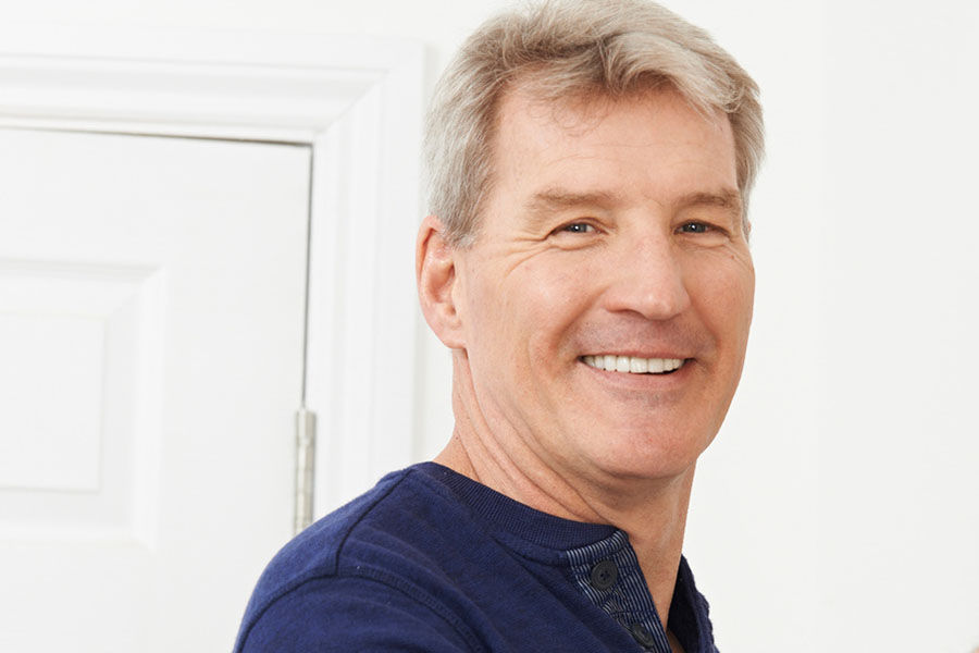 Middle aged handy man takes a break working to show off his amazing smile