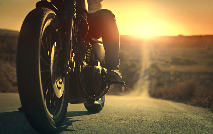 On a roaring motorcycle at sunset