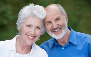 Older loving couple show off their amazing smiles