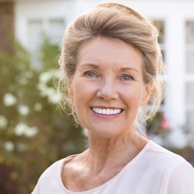 A elderly woman with new porcelain veneer revisions in Irvine CA
