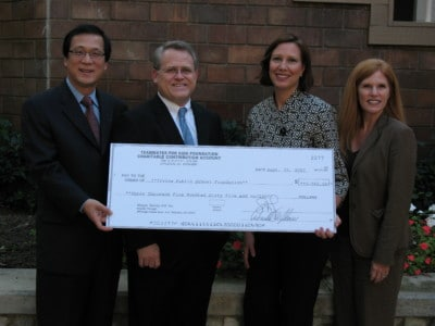 An oversized check from Rice Dentistry to the Irvine Public School Foundation