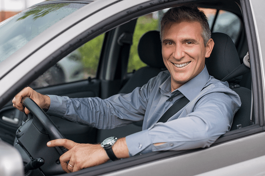 A man who recently completed orthodontic work smiles while sitting in his car.