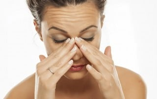 Woman holding ridge of nose. Is it a Sinus Infection or Tooth Infection?