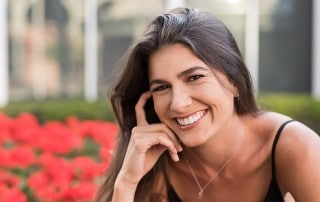 Pretty woman showing off her attractive smile all due to the help of dental implants making a natural, healthy look.