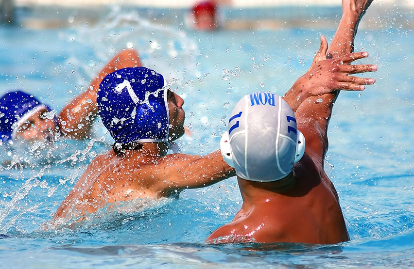 Three men competing in an aggressive game of water polo. The nature of the game creates numerous fast-moving arm swings, usually over the head, which increases the potential for head injury.