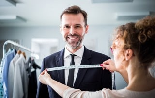 An older attractive business man gets his suit measured while he shows off his smile thanks to dental implants. A new study is investigating the health of gum tissue around dental implants. How do yours measure up?