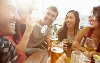 Young group of friends enjoy alcohol and laughter together on a warm patio