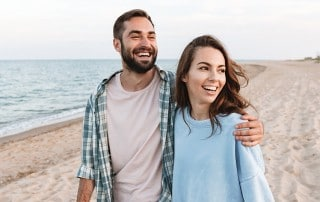 Beautiful young smiling couple spending time at the beach. For people who didn't get braces when they were young, how do you know now's the time to straighten your teeth?