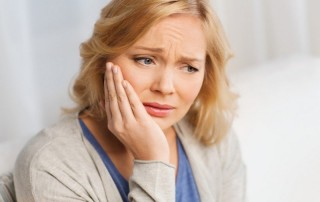 Middle aged woman holds jaw due to dental implant pain