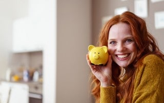 Redheaded woman shows off her yellow piggy bank while relaxing in her kitchen, enjoying her new smile. When considering cosmetic dentistry think about more than the just the cost!