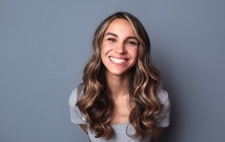 Young cheerful woman shows off her cheerful smile to the camera