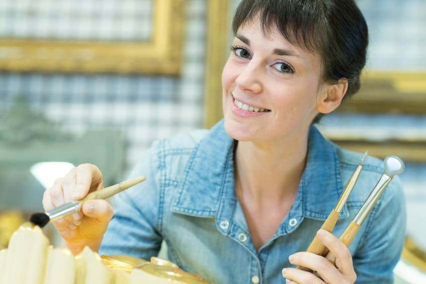Smiling Woman restoring a a work of art