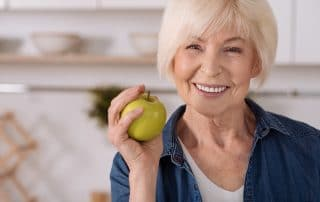 mature woman getting ready to eat an apple