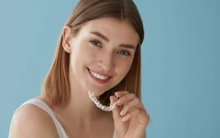 young woman prepares to place Invisalign clear braces in her mouth