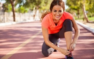 attractive woman pauses from running to tie her shoe