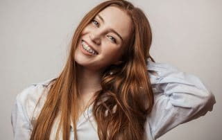 young red haired woman with traditional braces