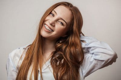 young red haired woman rests her hand behind her neck and shows off her smile with braces