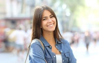 attractive young woman in denim jacket showing off her smile