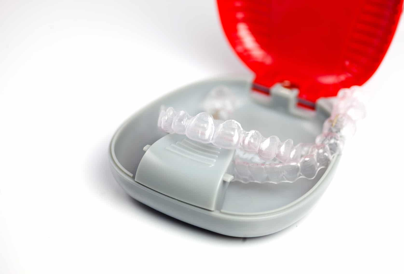 Clear orthodontic aligners in a red storage case on white