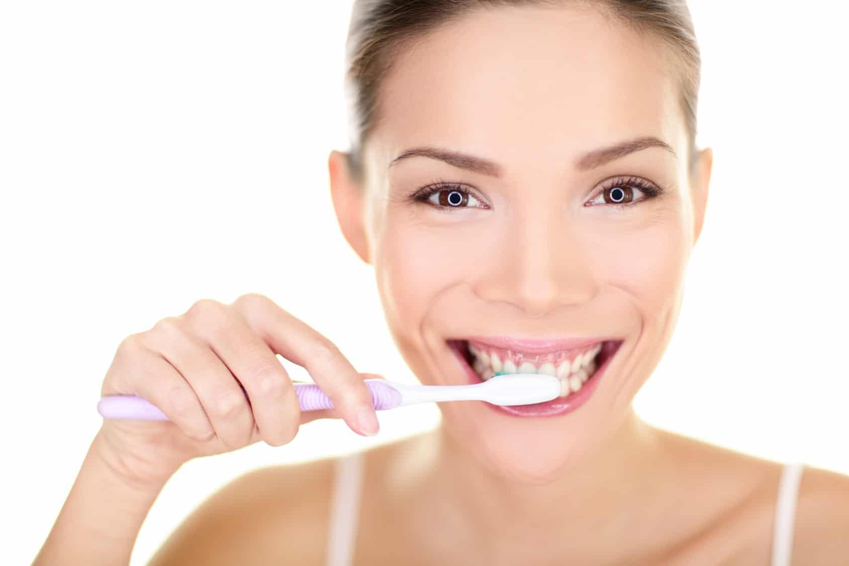 Woman brushing teeth holding toothbrush