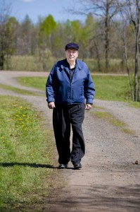 An elderly man walking a trail